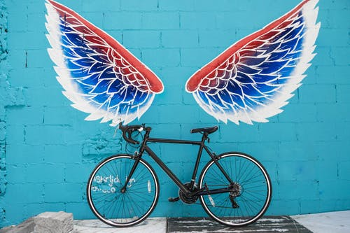 Bike on wall with wing painting