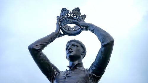 Statue of Man Holding Crown
