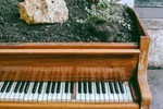 old wooden piano on city street